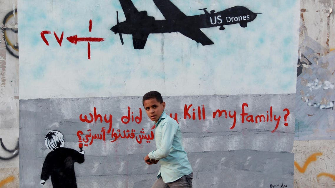 """A Yemeni boy (C) walks past a mural depicting a US drone and reading """" Why did you kill my family"""" on December 13, 2013 in the capital Sanaa. (AFP)"""