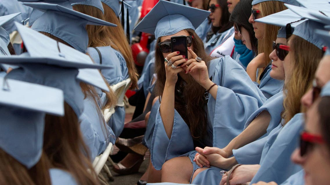 A graduate from Columbia University's Barnard College uses her a mobile phone to take a photo during the university's commencement ceremony in New York May 16, 2012. (Reuters)