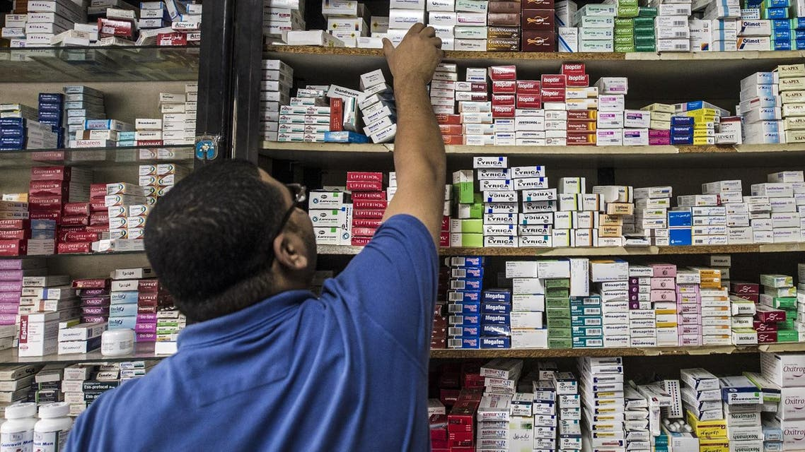 An Egyptian pharmacy employee reaches out to grab a box of medicine in a pharmacy in the capital Cairo. (AFP)