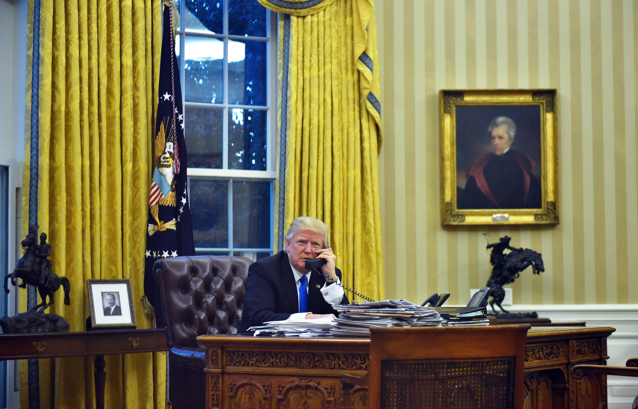 US President Donald Trump speaks on the phone with Australia's Prime Minister Malcolm Turnbull from the Oval Office of the White House on January 28, 2017, in Washington, DC. (AFP)