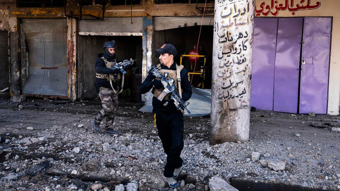 Members of the Iraqi special forces Counter Terrorism Service (CTS) walk next to destroyed shops in eastern Mosul on January 18, 2017. Iraqi forces have fully retaken east Mosul from the Islamic State group, a top commander said, three months after a huge offensive against the jihadist bastion was launched. (AFP)