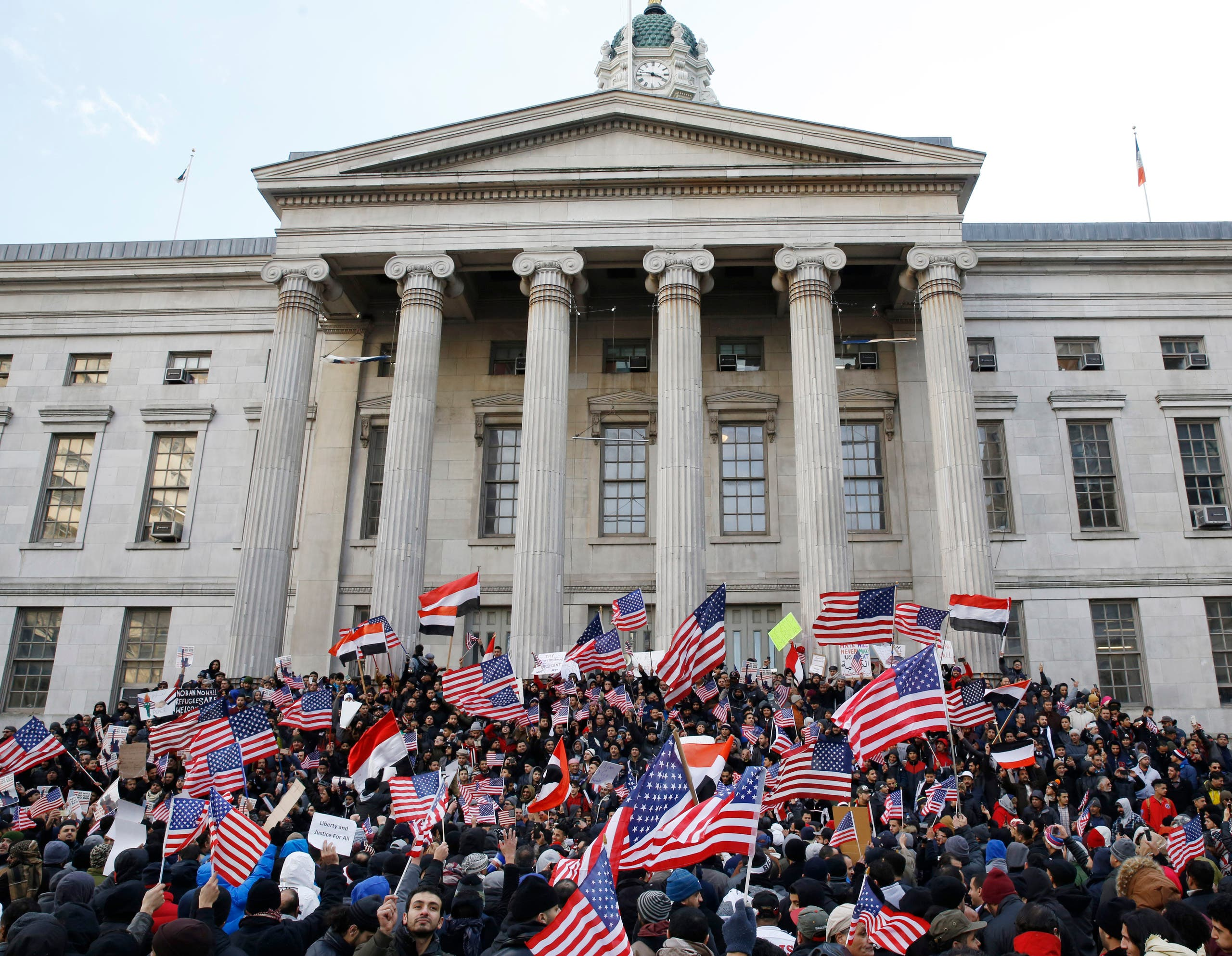 Muslims, members of the Yemeni community and others wave American and Yemeni flags as they gather on the steps of Brooklyn's Borough Hall to protest President Donald Trump's temporary travel ban on citizens from seven predominantly Muslim countries, Thursday, Feb. 2, 2017, in New York. (AP)