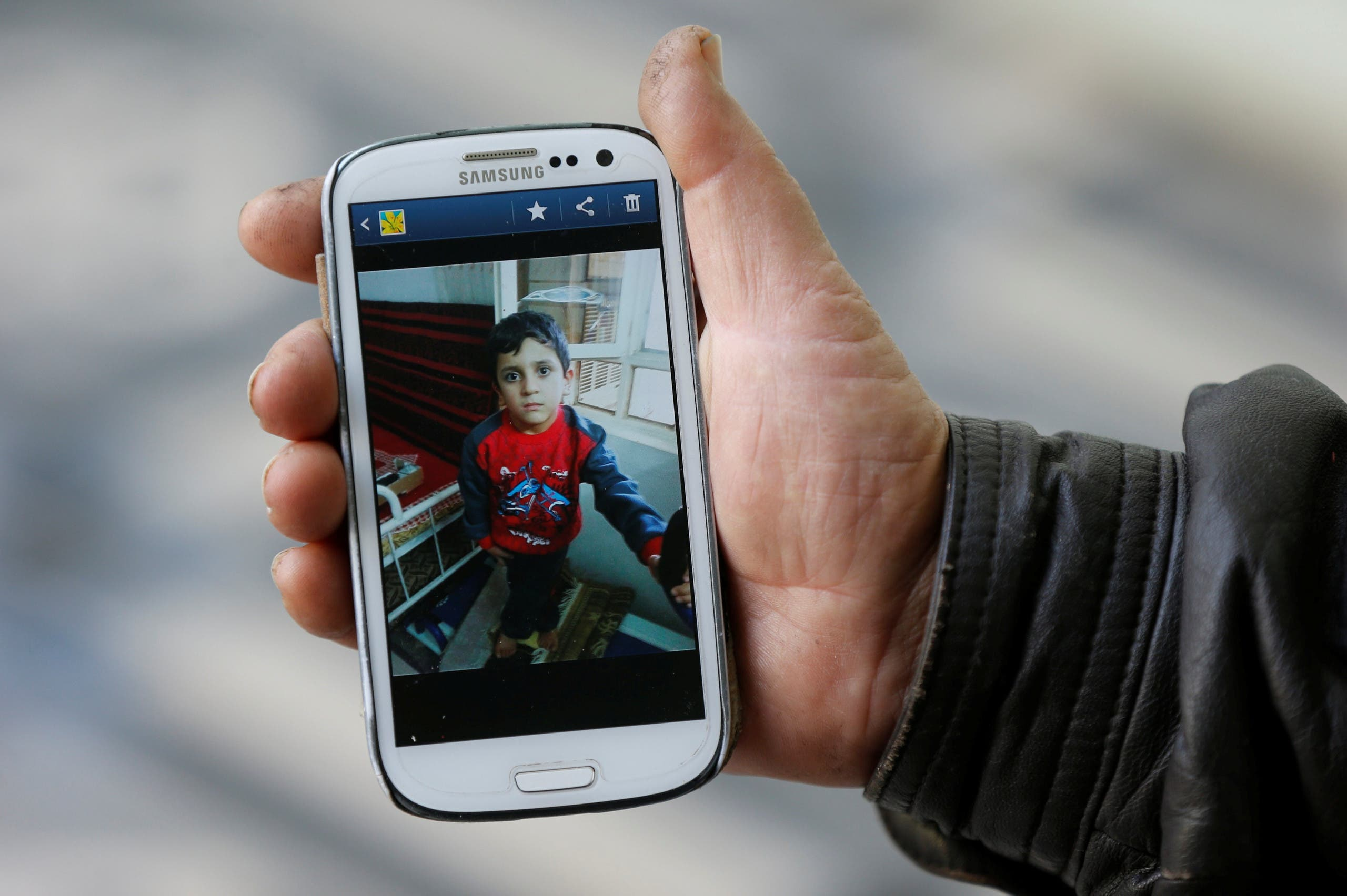 Abu Ahmed, who bought Yazidi boy Ayman from Islamic State militants in Mosul, shows a picture of Ayman on his phone in Rashidiya, north of Mosul, Iraq, January 30, 2017. reuters