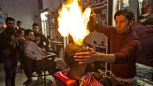 صور.. لماذا يستخدم هذا الحلاق النار فوق رؤوس زبائنه؟