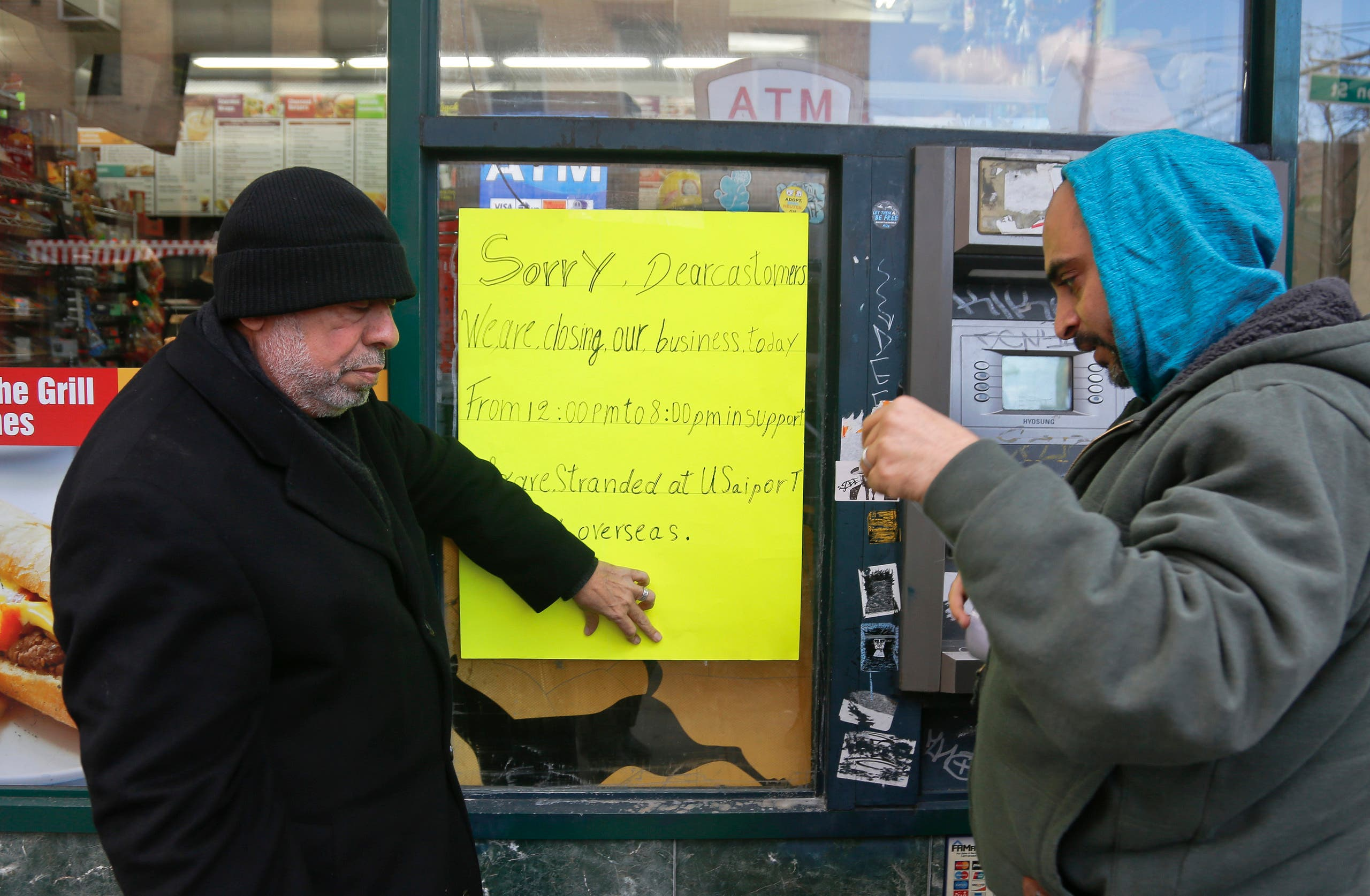 Zamood Zokari, left, and Ali Elazab, right, post a sign on a window of Zokari' family deli in lower Manhattan, alerting customers that the store will close because of a protest against President Donald Trump's travel ban, Thursday, Feb. 2, 2017, in New York. ap