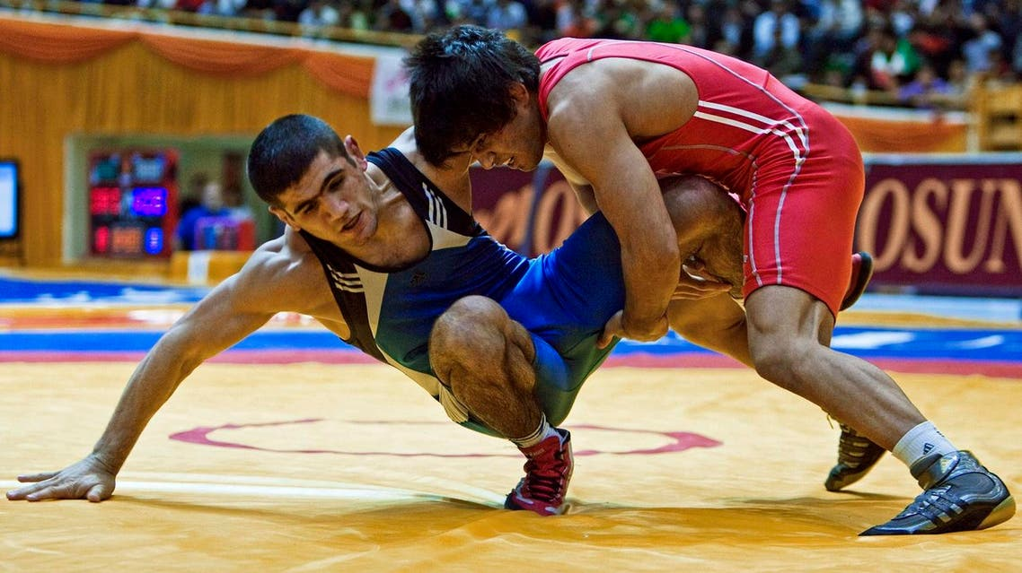 Mehdi Taghavi Kermani of Iran (in red) fights Jabrayil Hasanova of Azerbaijan during their 66kg men's wrestling match at the Tehran Freestyle World Cup competition March 8, 2009. REUTERS