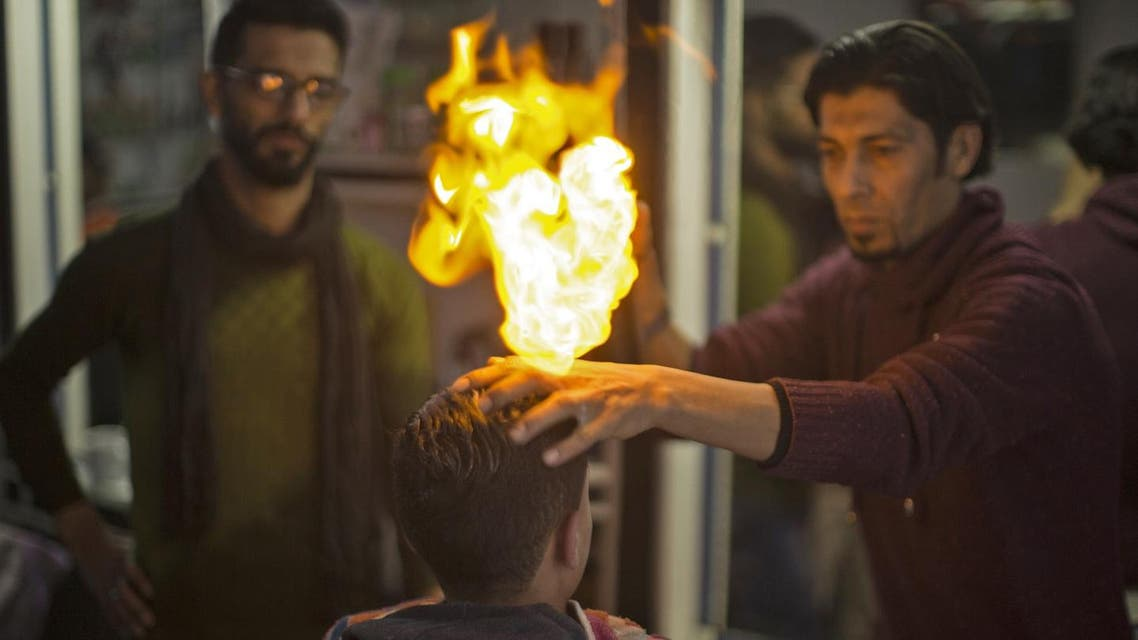 Ramadan Edwan, a Palestinian barber, uses fire in a hair-straightening technique with a client at his salon in the Rafah refugee camp, in the southern Gaza Strip on February 1, 2017.  AFP