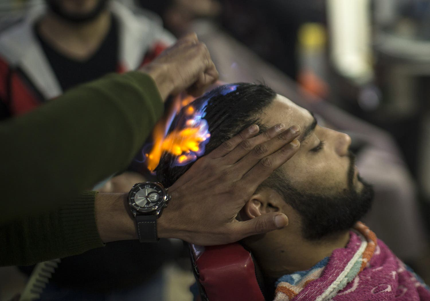 A client sits in a hair salon as barber Ramadan Edwan performs a technique that utilises fire to straighten his hair, in the Rafah refugee camp, in the southern Gaza Strip on February 1, 2017. MAHMUD HAMS / AFP