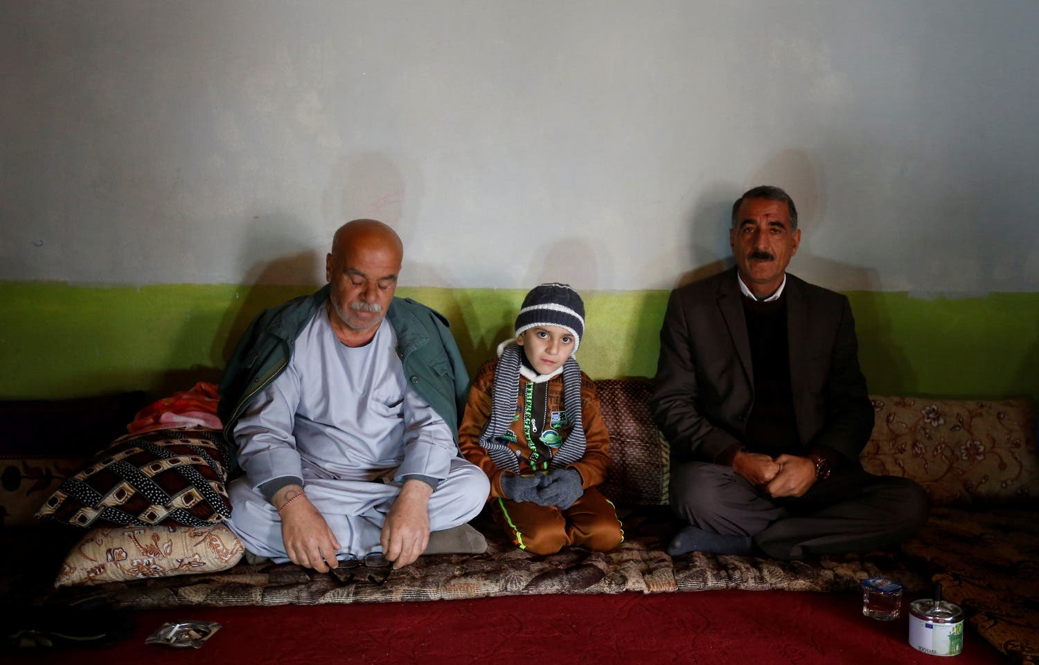 Ayman sits beside his uncle Samir Rasho Khalaf (L) after he was returned to his Yazidi family in Duhok, Iraq. (Reuters)