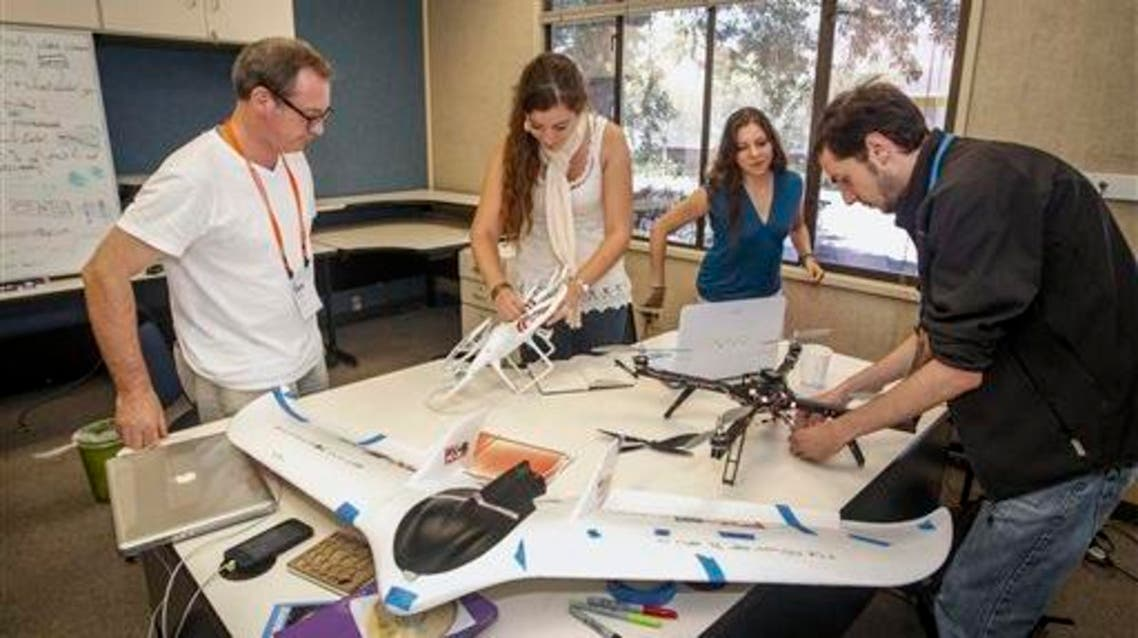 From left to right: Student advisor David Trayford, Victoria Alonsoperez, Uruguay, Lucia Pivaral, Guatemala, and Felipe Hernandez, Chile, works on using drones for monitoring agricultural development and conditions at Singularity University campus in Moffett Field, California. (AP)