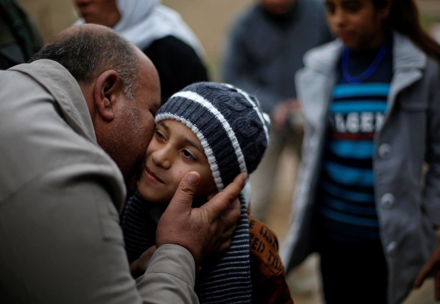 Ayman is greeted by his relative after he was returned to his Yazidi family in Duhok, Iraq. (Reuters)