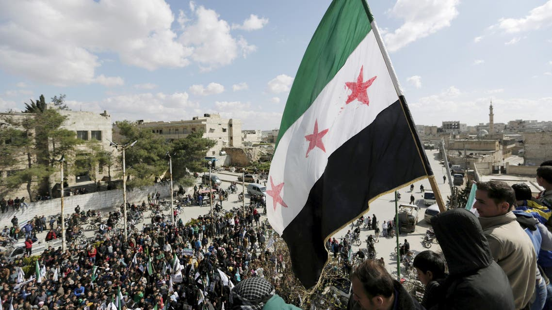 Men carry a Free Syrian Army flag while attending an anti-government protest in Maarat al-Numan, south of Idlib, Syria March 18, 2016. REUTERS/Khalil Ashawi