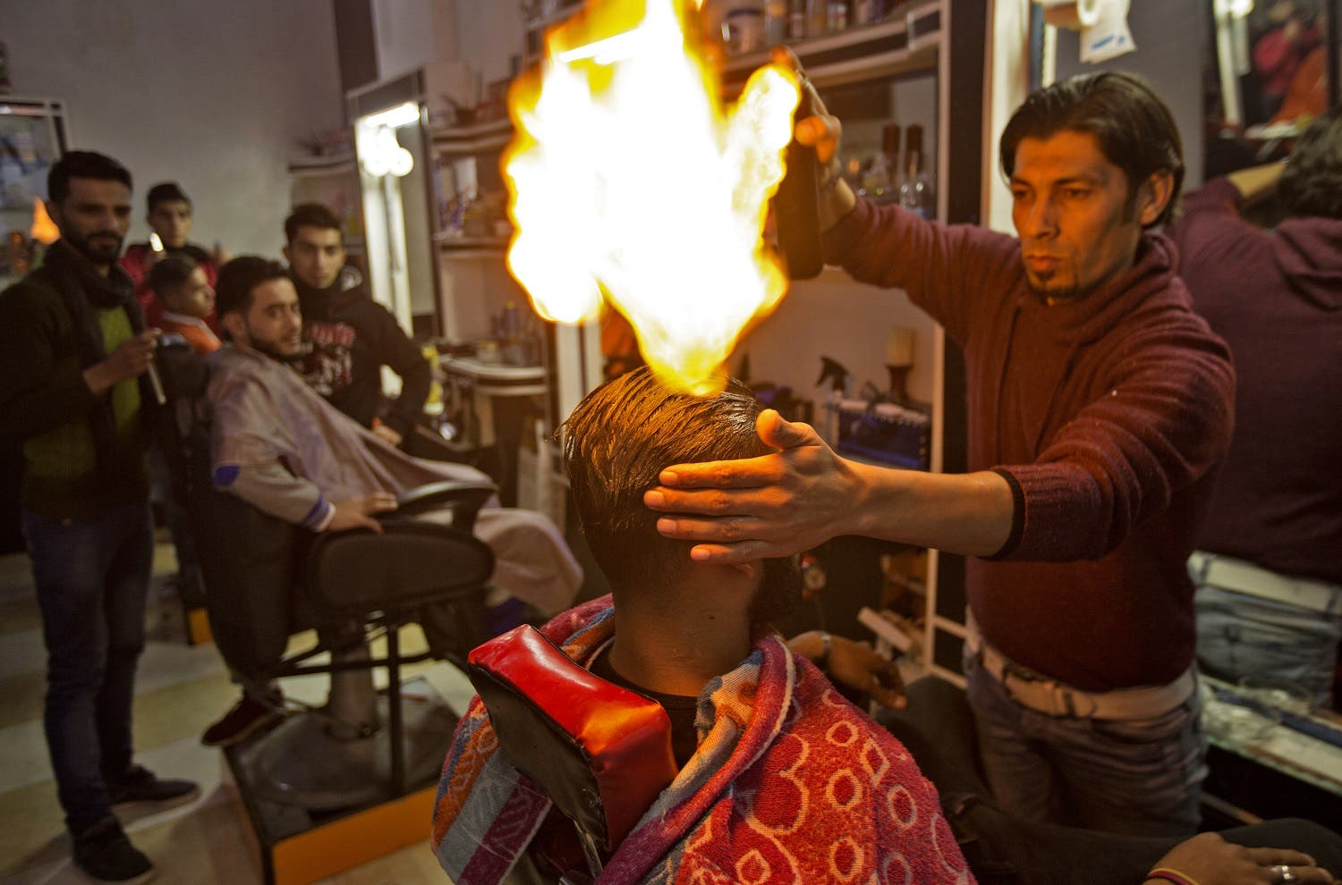 Ramadan Edwan, a Palestinian barber, uses fire in a hair-straightening technique with a client at his salon in the Rafah refugee camp, in the southern Gaza Strip on February 1, 2017.