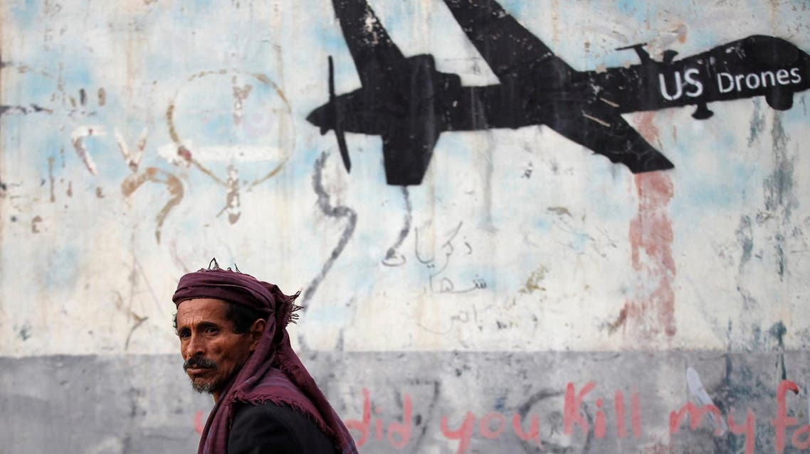 A man walks past a graffiti, denouncing strikes by U.S. drones in Yemen, painted on a wall in Sanaa, Yemen February 6, 2017. Picture taken February 6, 2017. REUTERS/Khaled Abdullah