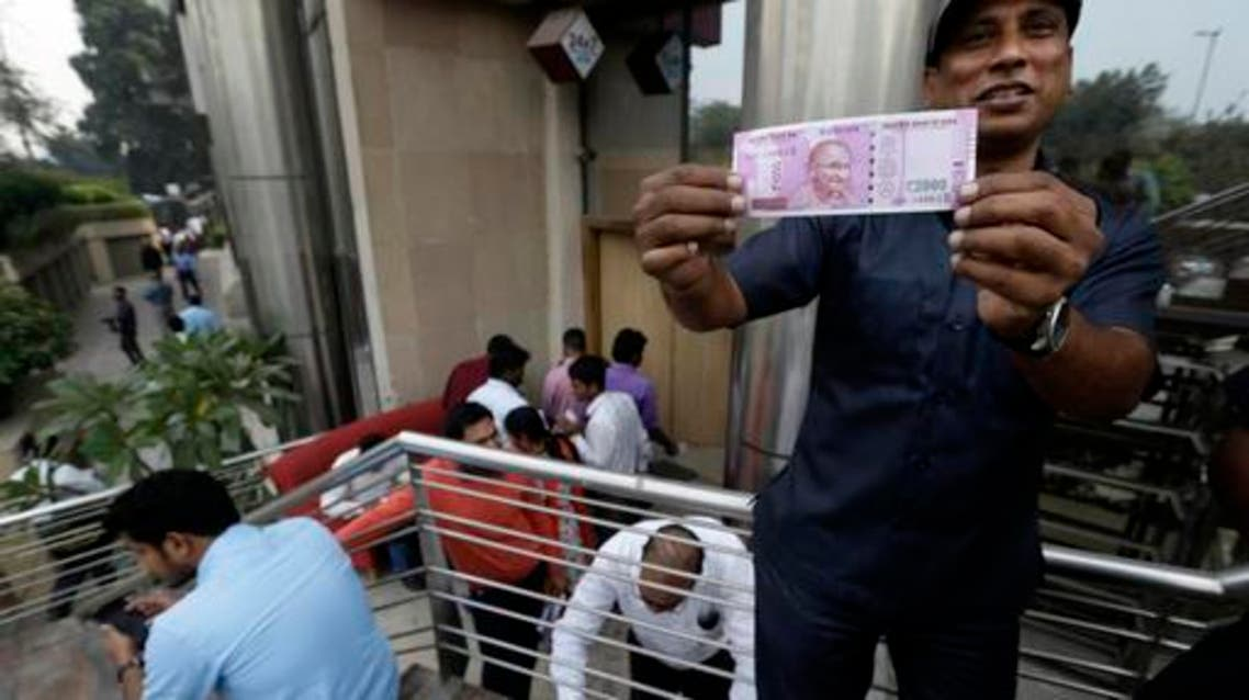 In this Nov. 10, 2016 file photo, a man displays a new Indian currency note of denomination 2000 that he received in exchange for discontinued currency notes outside an Axis Bank branch in central New Delhi, India. (AP)