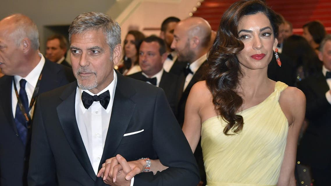 """George Clooney and Amal Clooney leave on May 12, 2016 the Festival Palace after the screening of the film """"Money Monster"""" at the 69th Cannes Film Festival in Cannes, southern France. (AFP)"""