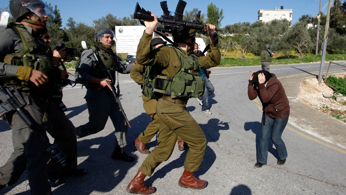 An Israeli soldier raises his weapon towards a Palestinian woman during scuffles in the West Bank village of Nabi Saleh near Ramallah in this January 22, 2010 file photo. rreuters
