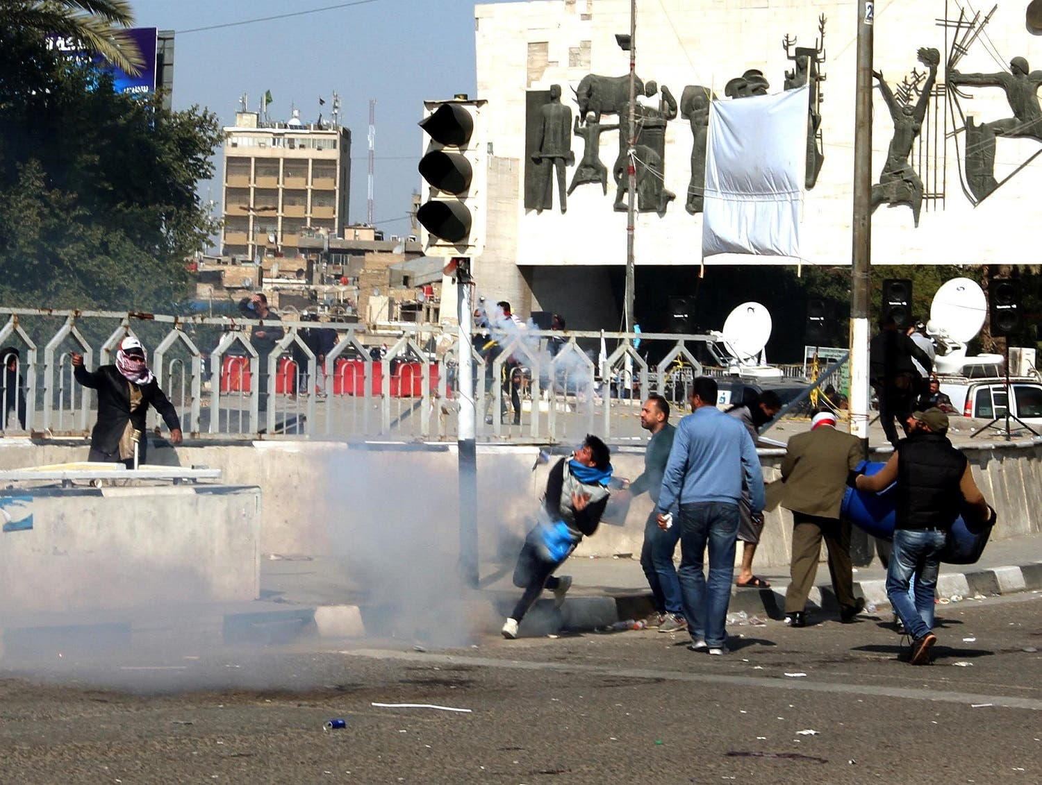 Protesters run from tear gas fired by security forces after Sadr supporters tried to approach the heavily fortified Green Zone during a protest at Tahrir Square in Baghdad. (Reuters)