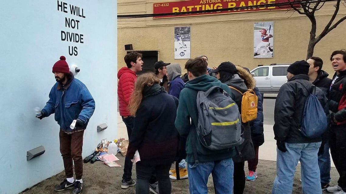 """Actor Shia LeBeouf, left, stands in front of a live-steam camera with the words """"HE WILL NOT DIVIDE US"""" posted on a wall outside of the Museum of the Moving Image as members of the public join LeBeouf in chanting (Photo: AP/Deepti Hajela)"""