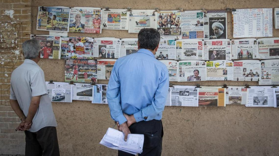 People looking at newspapers for sale on a wall in Yazd, Iran. (Shutterstock)