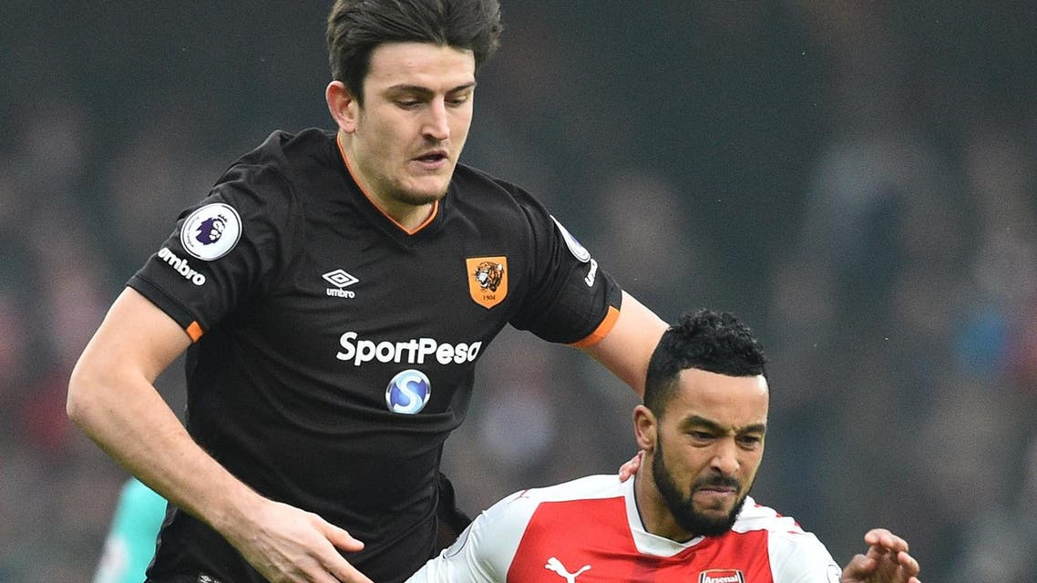 Harry Maguire and Theo Walcott. AFP