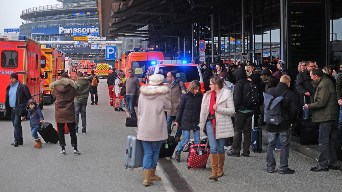 Firefighters with multiple vehicles stand in front of Hamburg airport as passengers leave the terminal on February 12, 2017 in Hamburg, northern Germany, as German emergency services evacuated the airport after people reported an unusual smell as well as respiratory ailments and watering eyes.