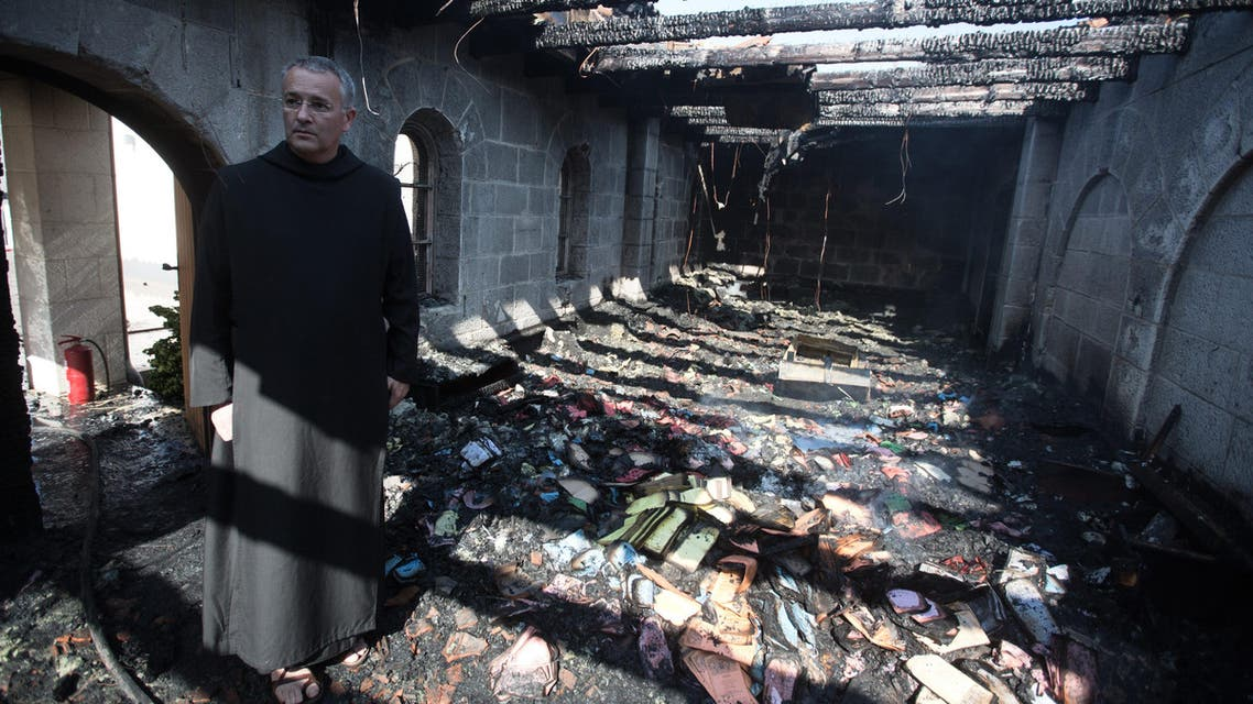 A priest inspects the damage at a room located on the complex of the Church of the Multiplication at Tabgha, on the shores on the Sea of Galilee in northern Israel, on June 18, 2015, in the aftermath of a suspected arson attack. The suspected attack totally destroyed an external atrium of the Christian shrine, which is believed by many Christians to be the place where Jesus fed the 5,000 in the miracle of the five loaves and two fish, with a church adviser pointing the finger at Jewish extremists. AFP PHOTO / MENAHEM KAHANA