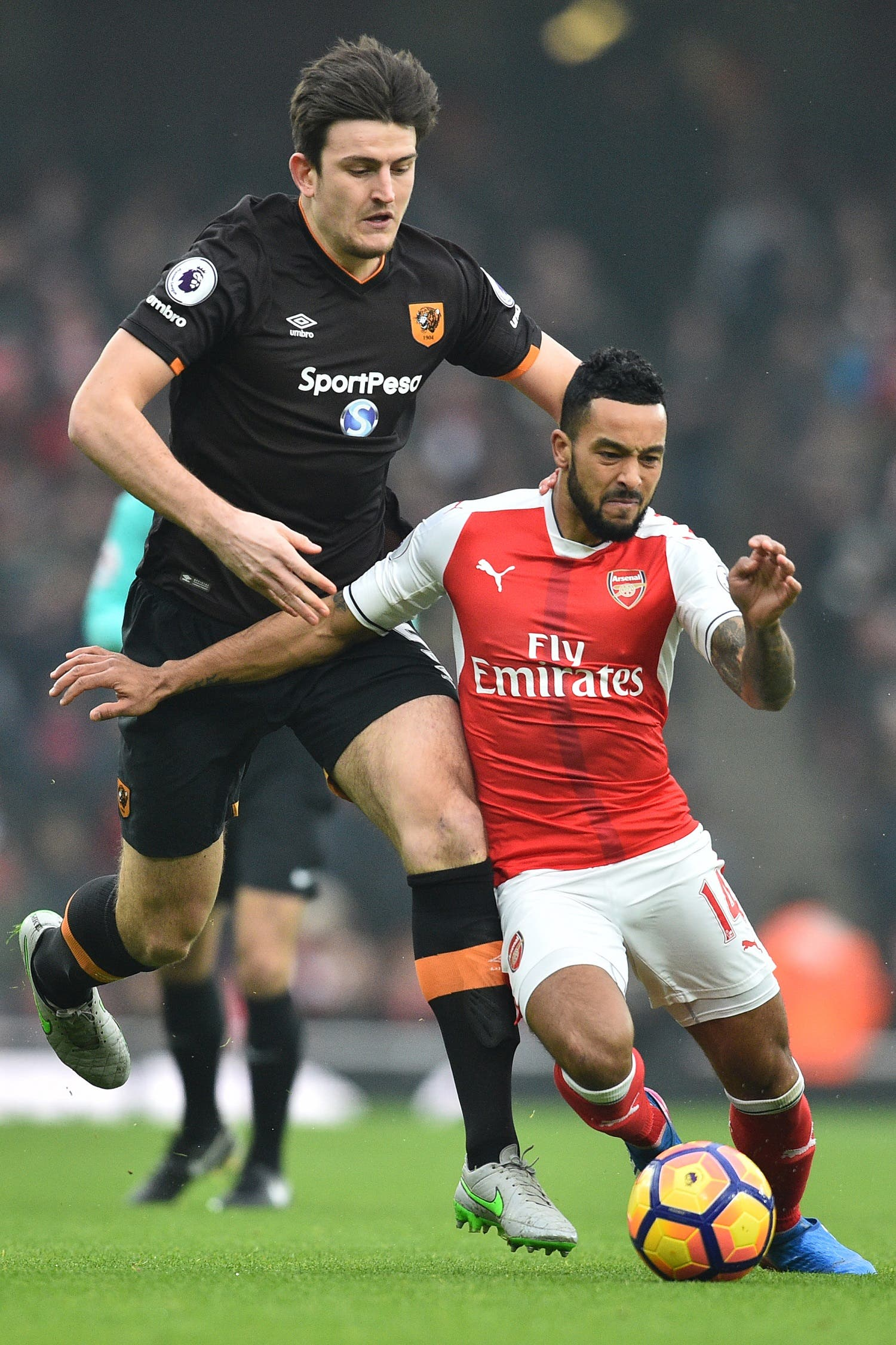 Theo Walcott (L) and Harry Maguire (R) AFP.