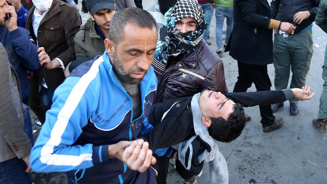 An injured man is assisted after reacting to tear gas fired by security forces during a protest by followers of influential Iraqi cleric Muqtada al-Sadr (Photo: AP/Karim Kadim)