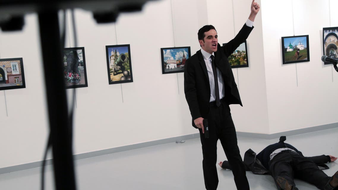 A man identified as Mevlut Mert Altintas shouts after shooting Andrei Karlov, the Russian Ambassador to Turkey, at a photo gallery in Ankara, Turkey, Monday, Dec. 19, 2016.