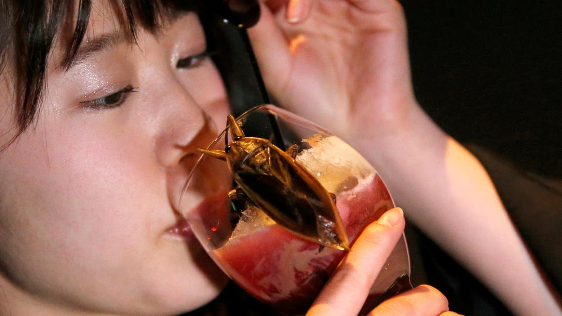 A woman drinks a cocktail with whipped cream containing juice of water bugs at a bar in downtown Tokyo, Japan, February 12, 2017. reuters