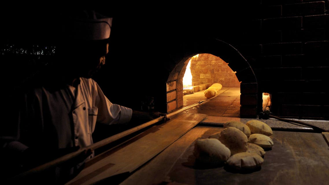 A foreign baker removes bread from the oven at a bakery in the Saudi Red Sea city of Jeddah on July 7, 2011