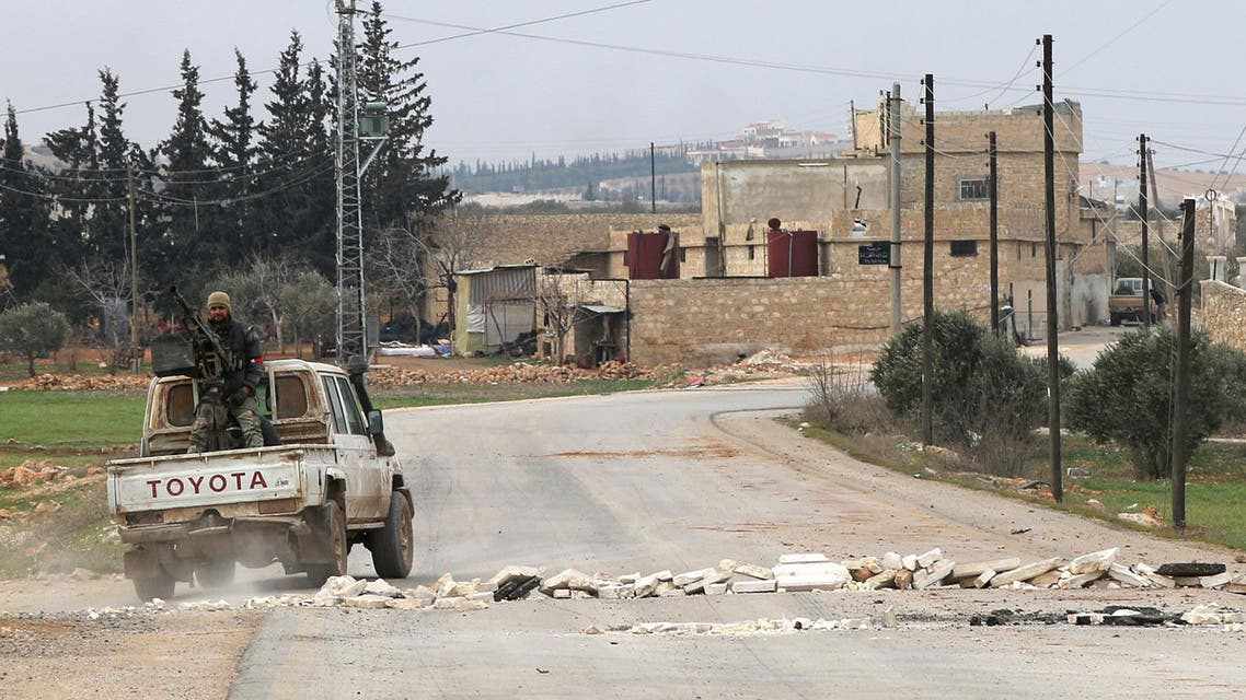 Opposition fighters backing Turkish troops drive past stones blocking a road in the village of Hazwan on the outskirts of the Syrian town of al-Bab as they advance towards the town which is the last stronghold of the Islamic State (IS) group in Syria's Aleppo's province on February 12, 2017.