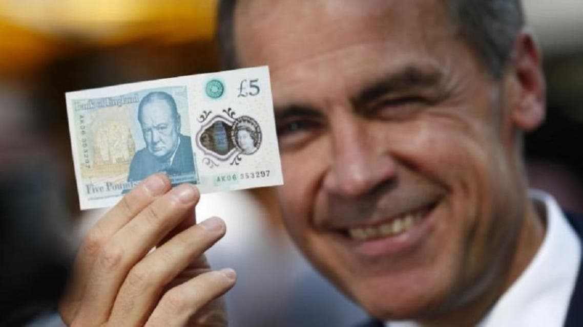 Bank of England governor Mark Carney poses with a new polymer five pound note at Whitecross Street Market in London, Britain September 13, 2016. (Reuters)