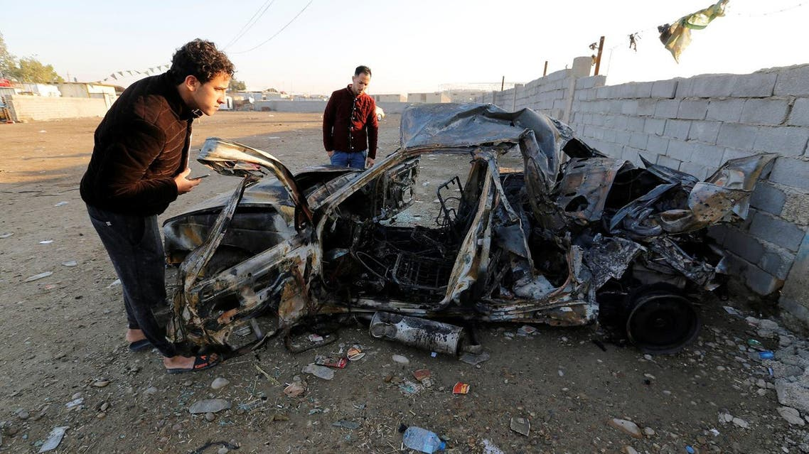 Men look at the wreckage of a burnt car after a suicide bomber detonated a pick-up truck on Wednesday in Sadr City. (File photo: Reuters)