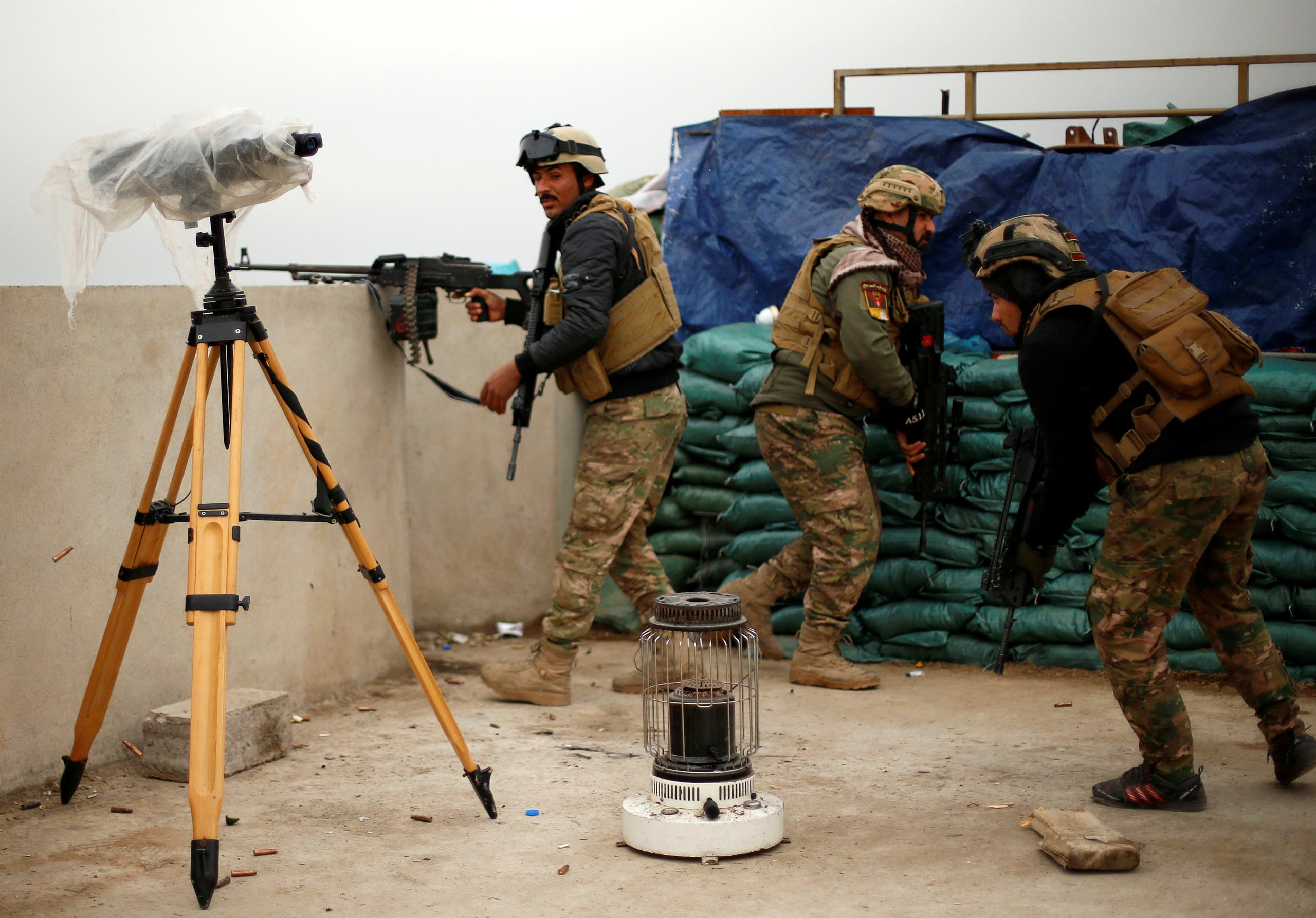 عنصر من قوات التدخل السريع العراقية يطلق النار على عناصر داعش عبر نهر دجلة بالموصل