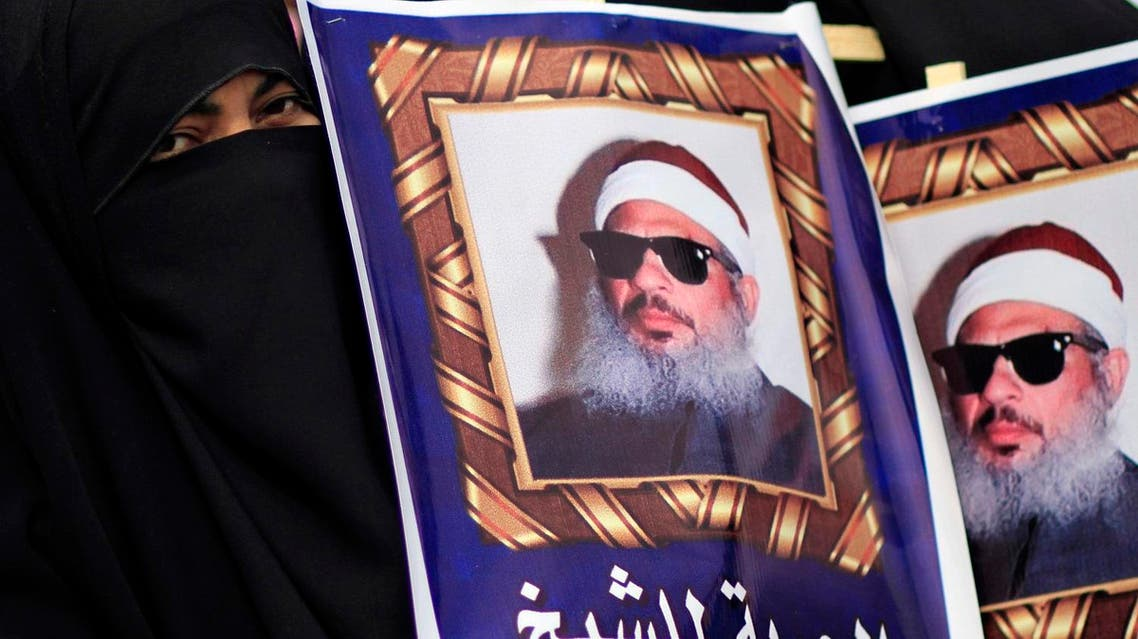 Egyptian Muslim Brotherhood protesters hold posters showing Sheikh Omar Abdel-Rahman calling for his release outside a court in Cairo in Feb. 26, 2012. (AP)