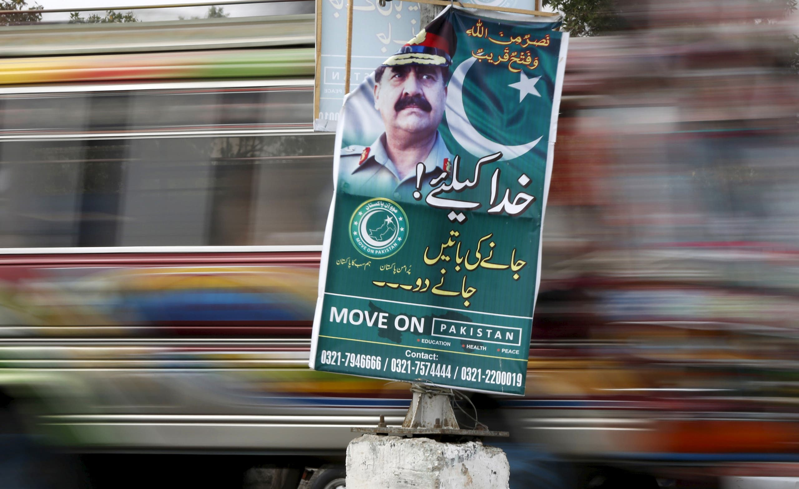 A bus moves past a banner hanging on a light pole with the picture of Pakistan's Army Chief of Staff General Raheel Sharif along a road in Karachi, Pakistan February 25, 2016. REUTERS/Akhtar Soomro