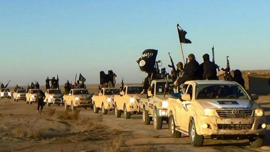 ISIS militants hold up their weapons and wave its flags on their vehicles in a convoy on a road leading to Iraq, in Raqqa, Syria. (Militant photo via AP)