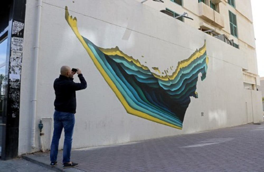 A man takes a picture of graffiti by Tunisian street artist The Inkman on a wall of Dubai's 2nd of December street. (AFP)