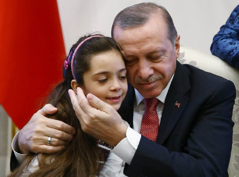 Turkey's President Recep Tayyip Erdogan (right) posing as he holds in his arms the seven-year-old Bana al-Abed (left), who tweeted from Aleppo on the attacks, at the Presidential Complex in Ankara. (AFP)