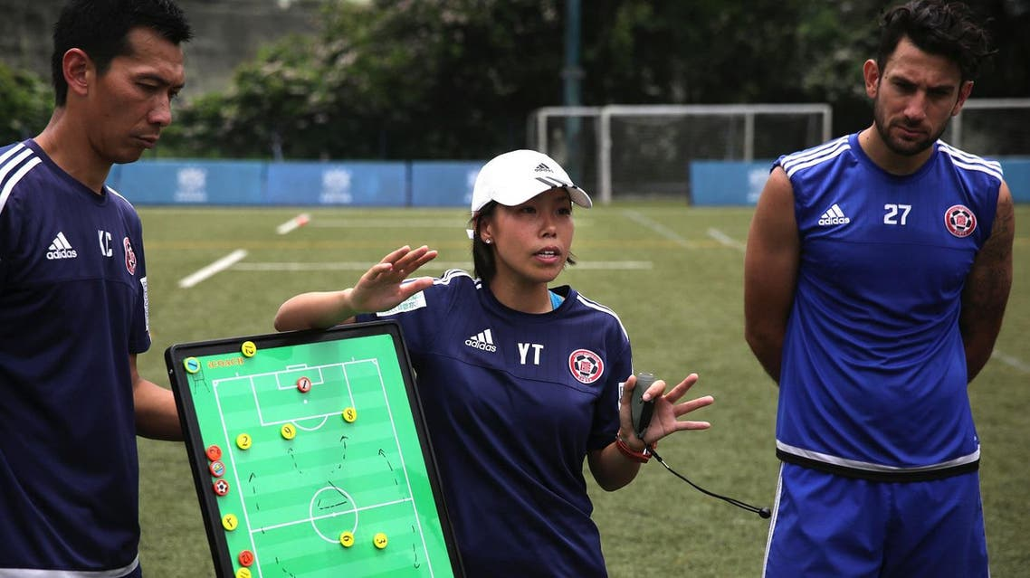 This picture taken on May 11, 2016 shows head coach of Eastern Football club Chan Yuen-ting (C) talking to her players during a team training session in Hong Kong. (AFP)