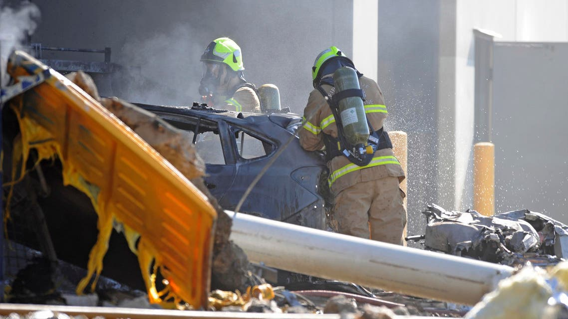Firemen help put out the blaze resulting from the plane crash. (AP)