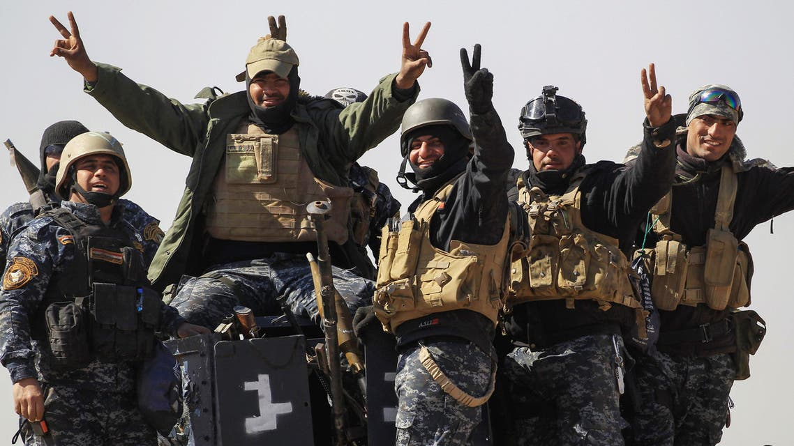 Members of the federal police react as they arrive in Albu Saif, which was recently retaken by Iraqi military forces, south of Mosul, Iraq February 22, 2017