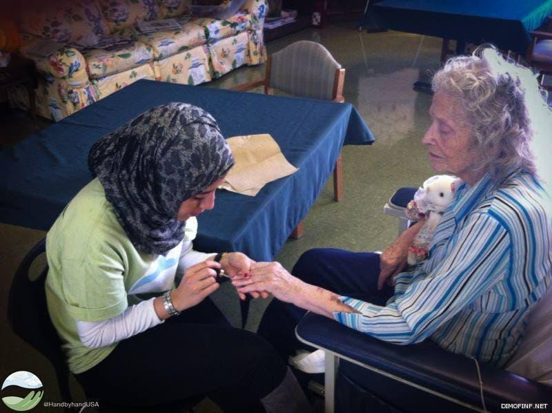 متطوعة في منظمة هاند باي هاند تخدم مسنة أميركية  بإحدى دور العجزة