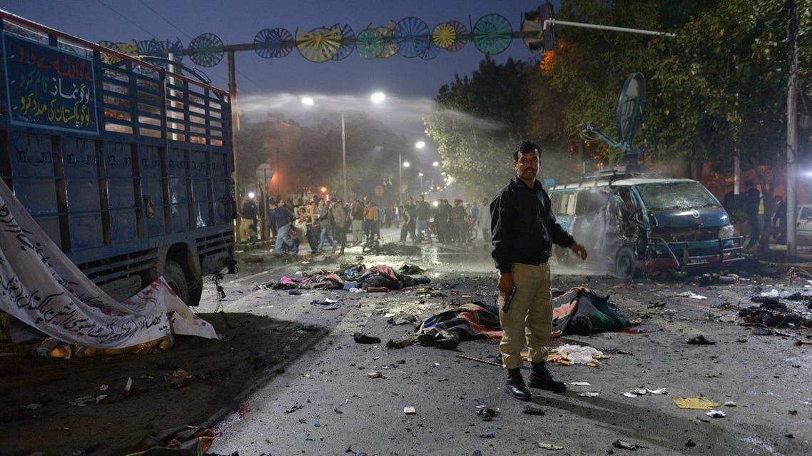 A Pakistani police officer stands alert beside the bodies of victims at the site after a powerful explosion in Lahore on February 13, 2017. (File photo: AFP)