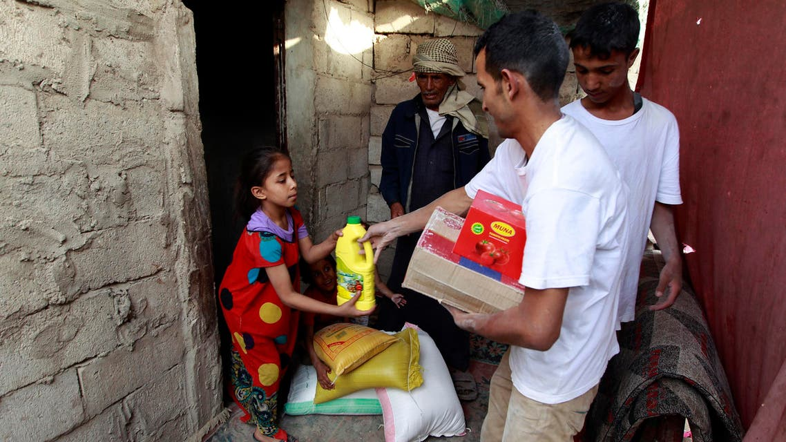 Yemeni volunteers of a local charity distribute food rations to families affected by the country's ongoing conflict on June 15, 2016 during the fasting month of Ramadan in an empoverished part of the capital Sanaa. (AFP)