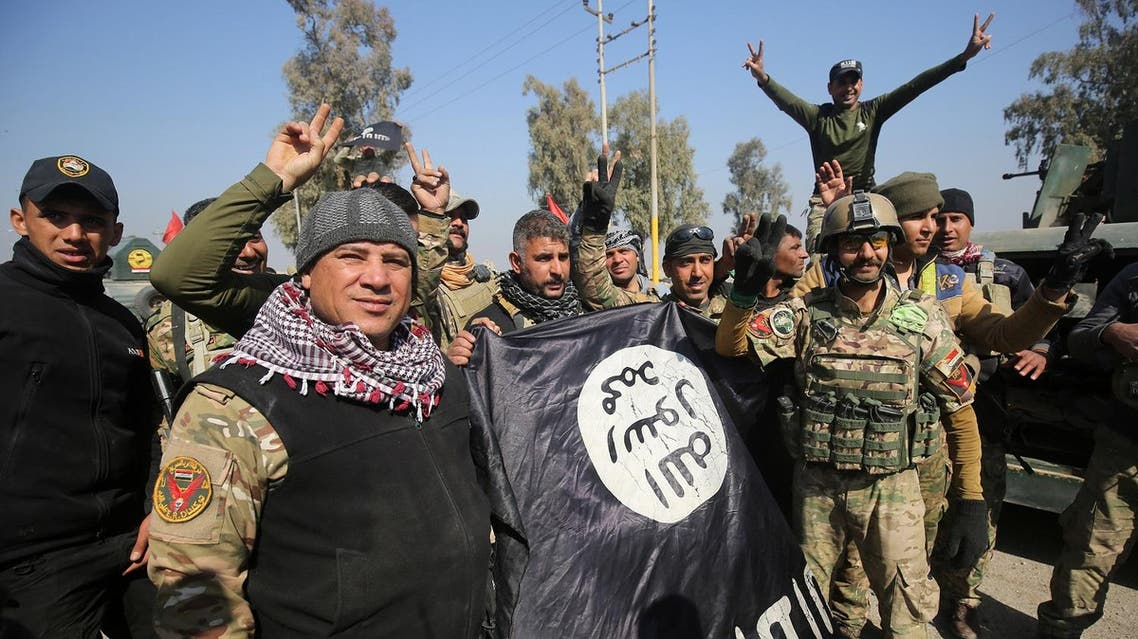 Iraqi forces flash the sign for victory while holding an Islamic State (IS) group flag on February 23, 2017, as they enter Mosul airport on the southern edge of the jihadist stronghold for the first time since the Islamic State group overran the region in 2014. (AFP)
