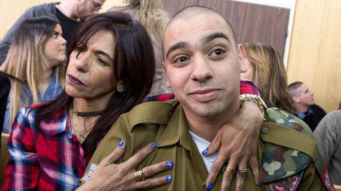 Israeli soldier Elor Azaria (R), who shot dead a wounded Palestinian assailant in March 2016, is embraced by his mother Oshra (L) at the start of his sentencing hearing in a military court in Tel Aviv on February 21, 2017. (AFP)