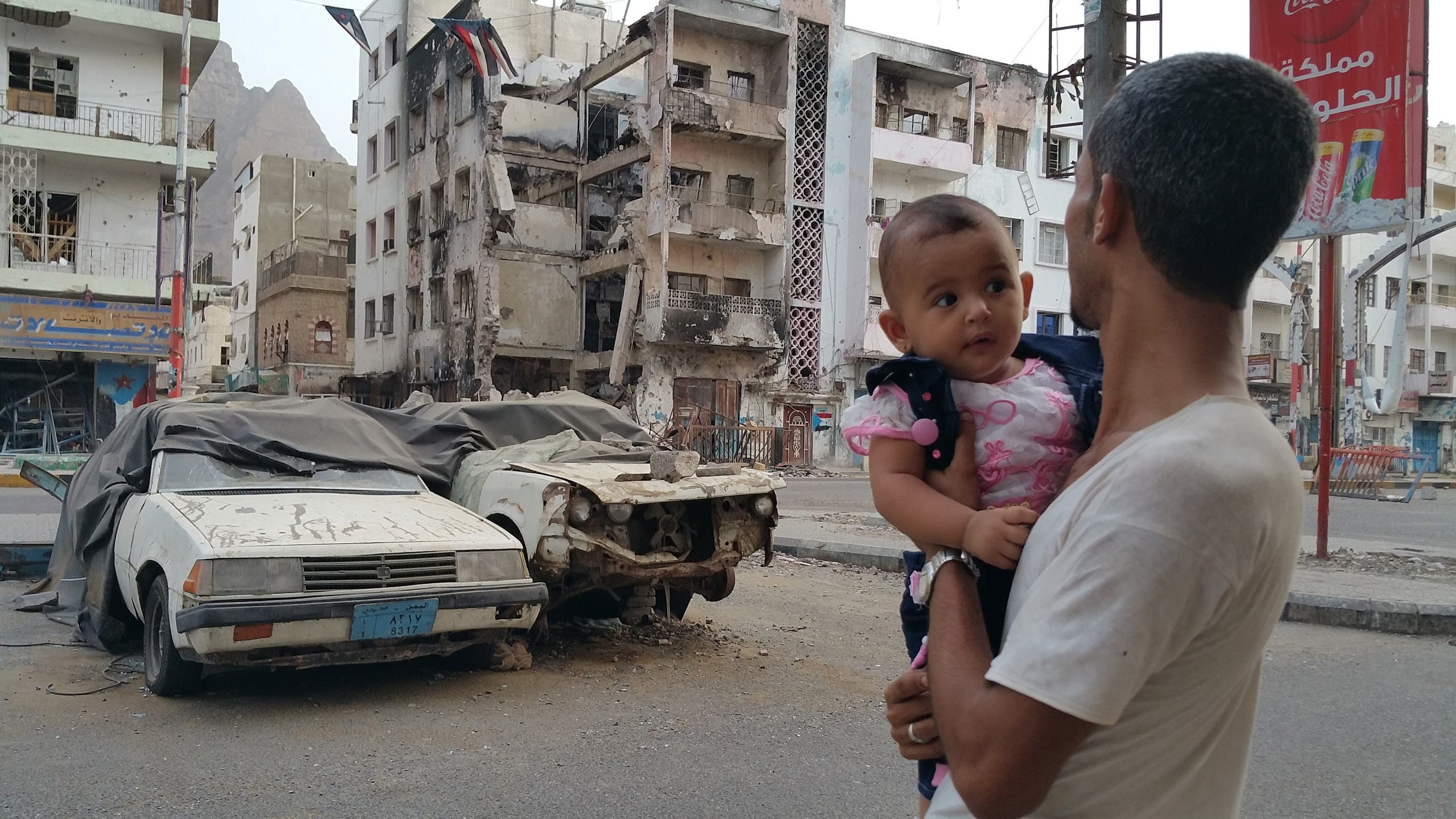 A Yemeni man carrying his daughter looks at a building destroyed during fighting against Houthi fighters in the port city of Aden, Yemen, Sunday, July 19, 2015.  AP